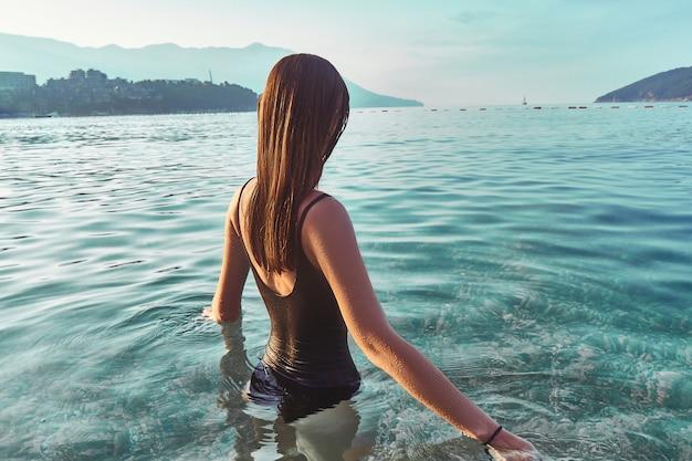 澄んだ青緑色の穏やかな水に立っている女性