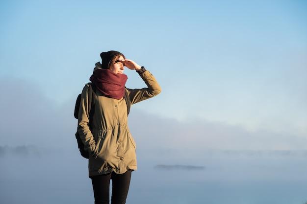 Женщина стоит в утреннем солнечном свете перед красивой природой, покрытой туманом. путешественница, наслаждаясь восходящим солнцем в туманном естественном фоне
