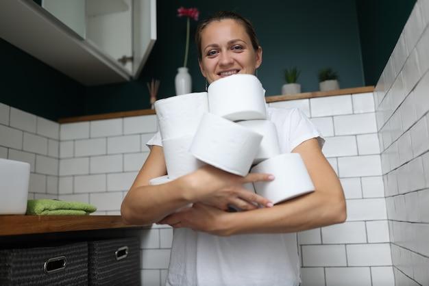 女性はトイレに立って、トイレットペーパーのロールのスタックを手に持っています。