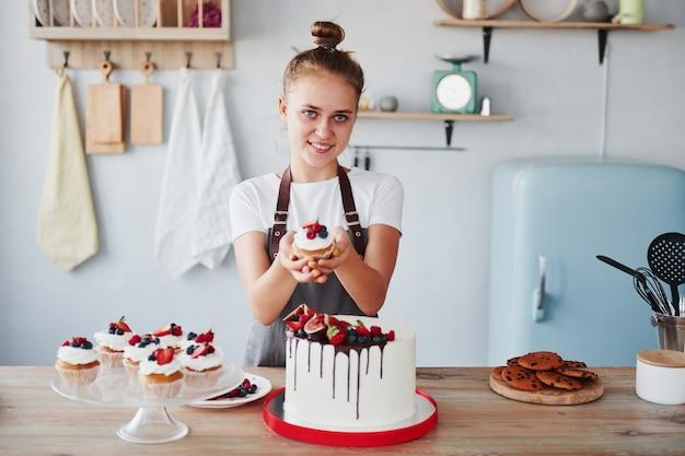 Женщина стоит в помещении на кухне с домашним пирогом.