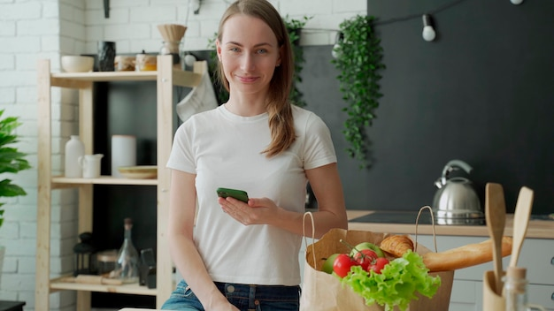 Woman stands in the kitchen near a paper bag full of fresh food and uses a smartphone app to deliver it to the supermarket