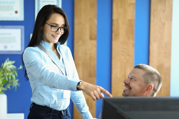 Woman stands next to man in office and points with her hand to manitor.