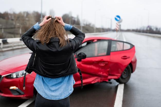 事故後、壊れた車の近くに立っている女性が自動車保険の助けを求めた