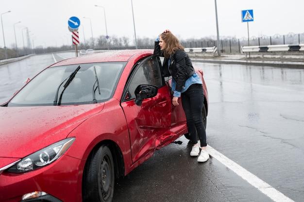 Женщина стоит возле разбитой машины после аварии. звать на помощь. страхование автомобиля