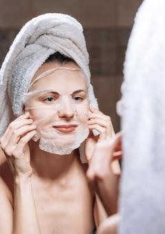 女性は頭にタオルを持って鏡の近くに立ち、化粧マスクを着用します