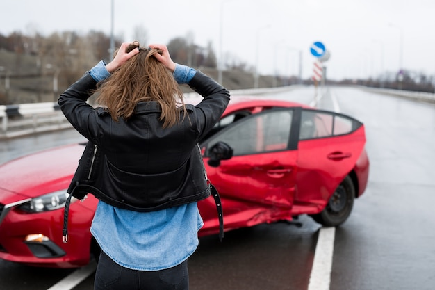 Woman stands near a broken car after an accident call for help car insurance