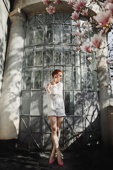 Woman stands near a building and a blossom magnolia