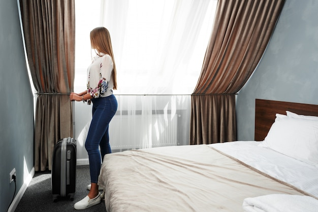 Woman stands near the window in hotel room at morning time