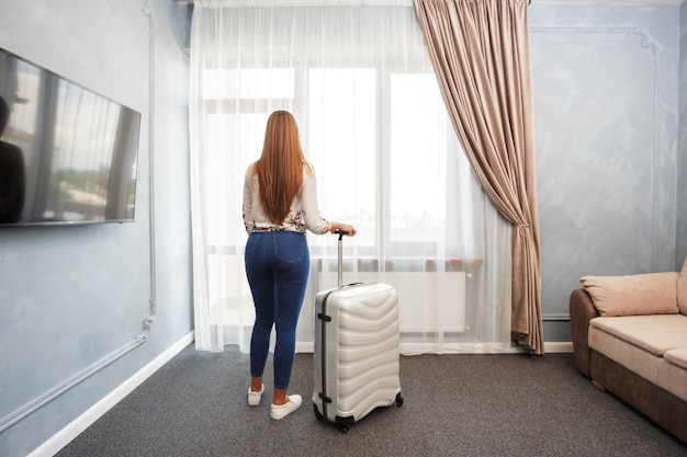 Woman stands near the window in hotel room at morning