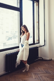Woman stands near the window in the morning