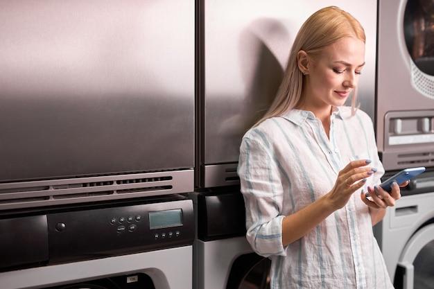 女性は携帯電話を使って洗濯機の隣に立ち、洗濯の終わりを待っています。洗濯屋で金髪白人女性女性