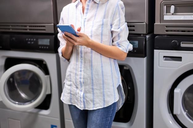 女性は携帯電話を使って洗濯機の隣に立ち、洗濯の終わりを待っています。洗濯屋で認識できない女性を切り取った