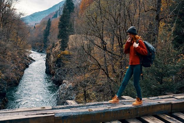 山の秋の森旅行で川に架かる橋の上に立つ女性