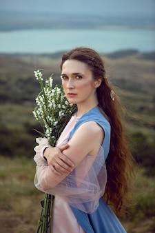 女性は夏に青いロングドレスで山の崖の上に立っています