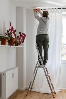 여자는 창문 근처의 접사 다리에 서서 커튼 막대에 흰색 커튼을 걸어