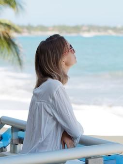 Женщина стоит на террасе у океана и дышит свежим воздухом.