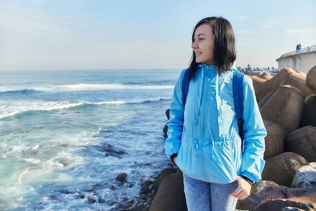 여자는 대서양의 해안에 서 있으며, 거센 파도가 해안, 파도를 치고 있습니다. 카사블랑카, 모로코