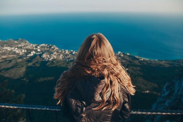女性は明るい端に立っています。山を旅する