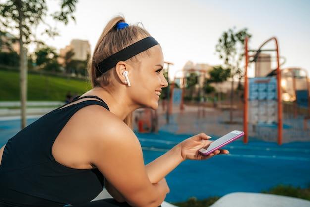 Una donna si trova presso la palestra all'aperto con un telefono