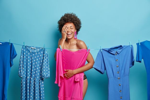 Woman stands shirtless near clothesline chooses dress to wear on date has cheerful expression makes palm smiles broadly isolated on blue