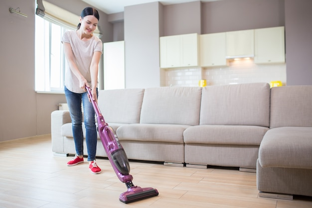Woman stands in studio apartment and cleaning the floor. she uses vacuum cleaner for that. girl is looking down.