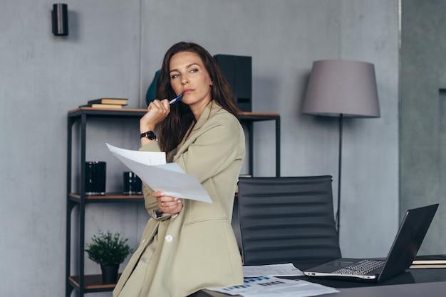 여자는 그녀의 책상에 기대어 그녀의 서류와 함께 신중하게 서있다.