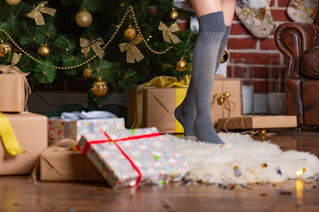 Woman stands on tiptoe in a warm gaiters on a fur rug in the room near the christmas tree with presents