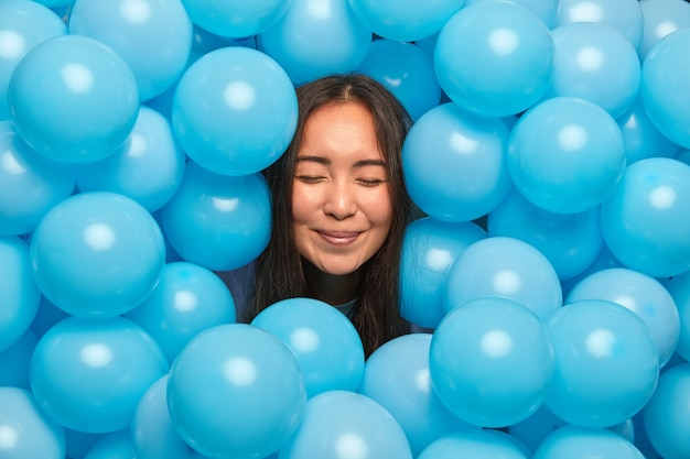 Woman stands with closed eyes sticks out head through blue inflated balloons