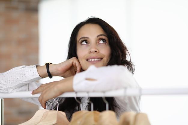 Женщина стоит, положив локти на вешалку, и мечтательно смотрит вверх