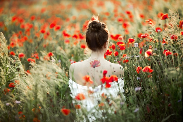 Woman stands with naked back, there is a tattoo flower poppy, among the poppies field