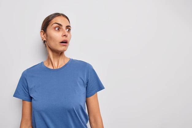 Женщина смотрит с застывшими глазами, затаив дыхание, одетая в повседневную футболку, не может поверить во что-то ужасающее на белом копировальном пространстве для промо