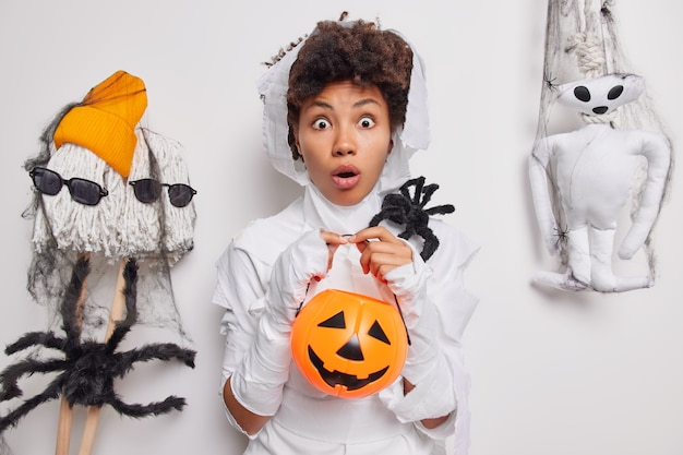Woman stares bugged eyes holds carved pumpkin and spooky spider poses on white with creepy creatures around. halloween decor