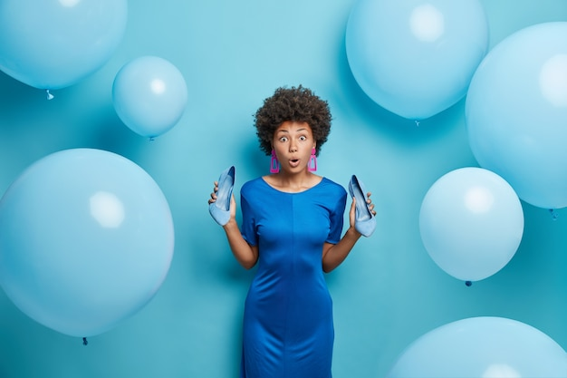 Woman stares impressed chooses outfit for special occasion going to have date poses indoor on flying airballoons isolated on blue
