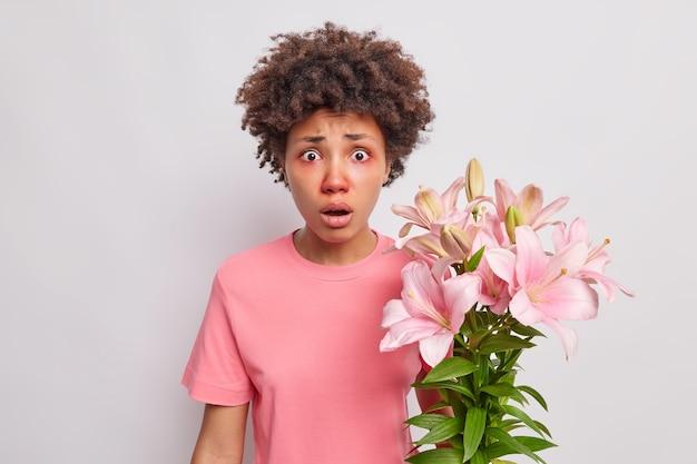 困惑した女性の視線はユリにアレルギー反応を示します顔の赤みは白で隔離されたカジュアルなtシャツを着ています