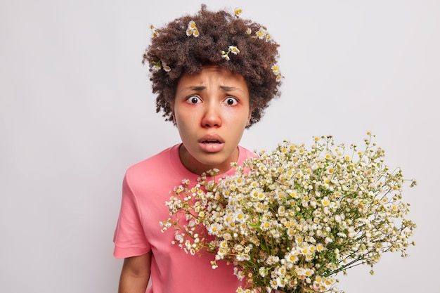 カモミールの花からの花粉に赤いかゆみのある目のアレルギーを持っている女性は唖然と心配して見つめ、白の上に分離された不快な症状に苦しんでいます