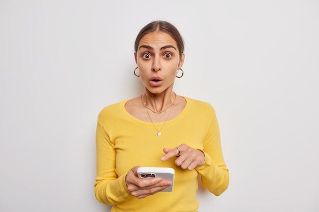 현대 스마트폰 화면에서 놀란 여성은 흰색 바탕에 노란색 스웨터를 입은 충격적인 놀라운 소식을 믿을 수 없다는 것을 나타냅니다.