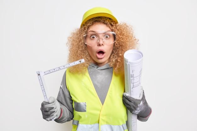 透明なメガネで驚いた女性の視線は、安全服を着た巻尺と建設計画を保持します