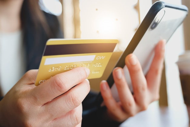 Woman stay at home and hand using credit card and phone for online shopping. online business marketing concept.