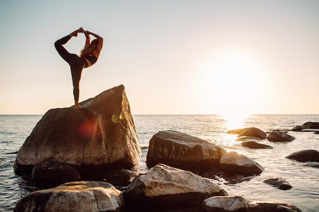 女性は夏の日没で穏やかな海のビーチでヨガをしている岩の上に滞在します。