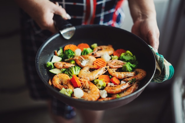 Женщина остается на домашней кухне и готовит креветки с овощами на сковороде. домашняя кулинария или концепция здорового приготовления