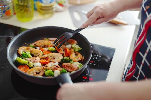 家庭の台所に滞在し、鍋に野菜とエビを調理している女性。家庭料理または健康的な料理の概念