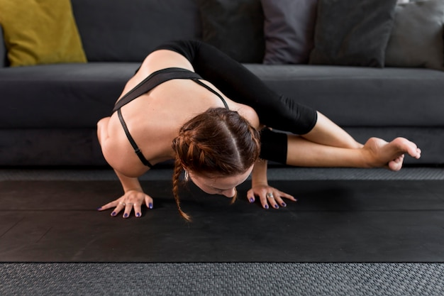 Woman staying in hands practicing yoga at home concept