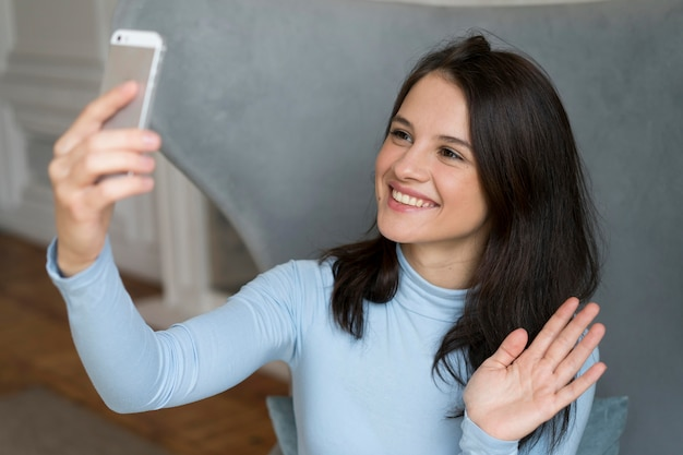 Woman staying in her bed while having a video call on her smartphone