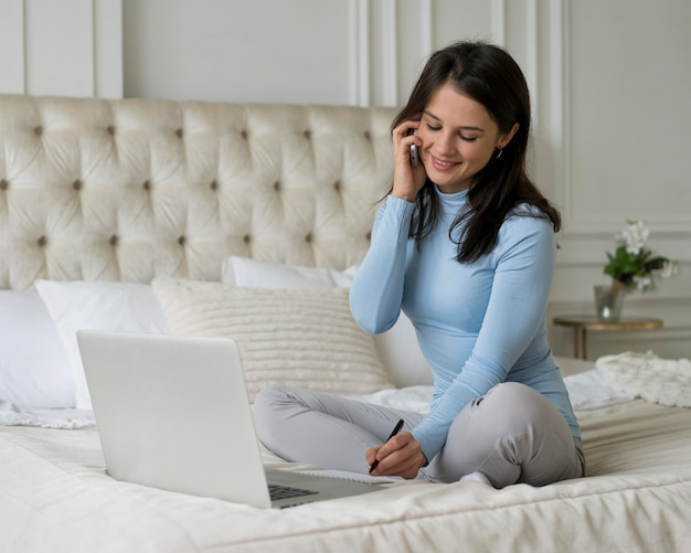 Woman staying in her bed while working