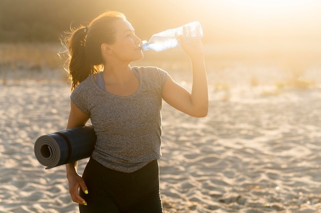 해변에서 운동하는 동안 수분을 유지하는 여자