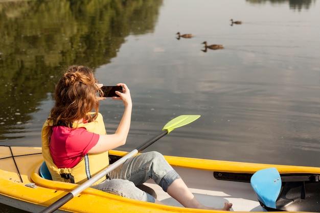 カヤックに滞在して写真を撮る女性