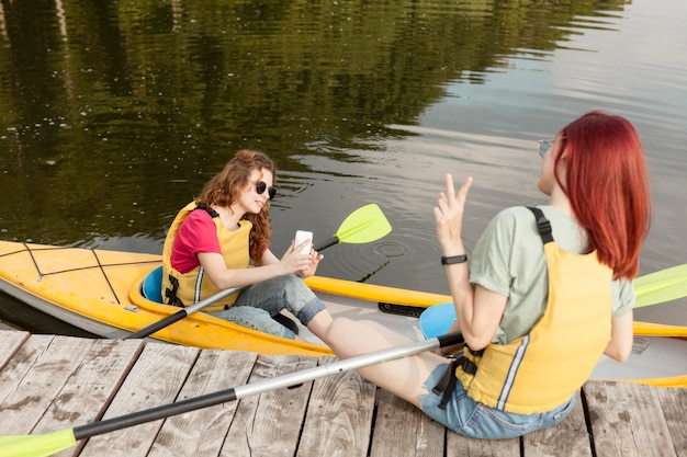 Woman staying in kayak and taking photos of friend