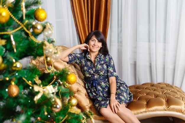 クリスマスツリーの近くのソファに滞在している女性