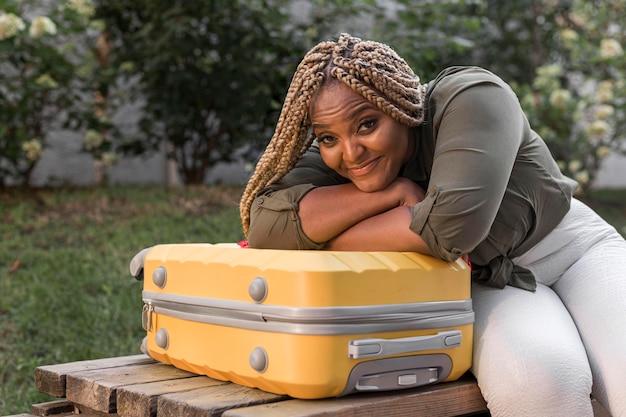 Женщина, стоящая на своем багаже с головой
