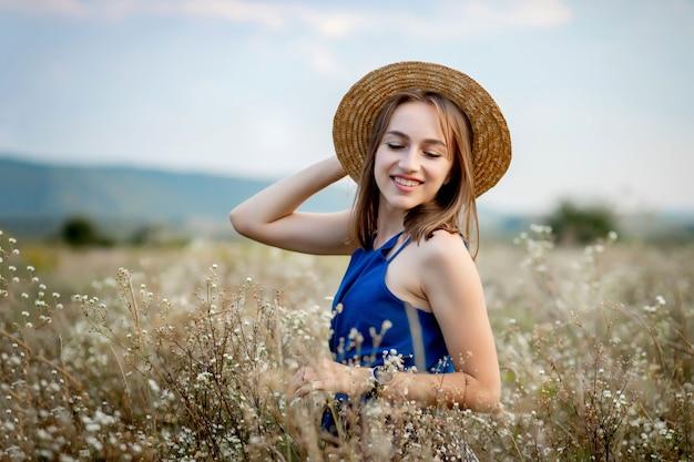 コピースペースを見ない野花畑にとどまる女性。スタイリッシュな服と帽子を身に着けている魅力的な若い女の子のブルネットの笑顔は農業の花の谷にとどまります。田舎の場所でかわいい女性。